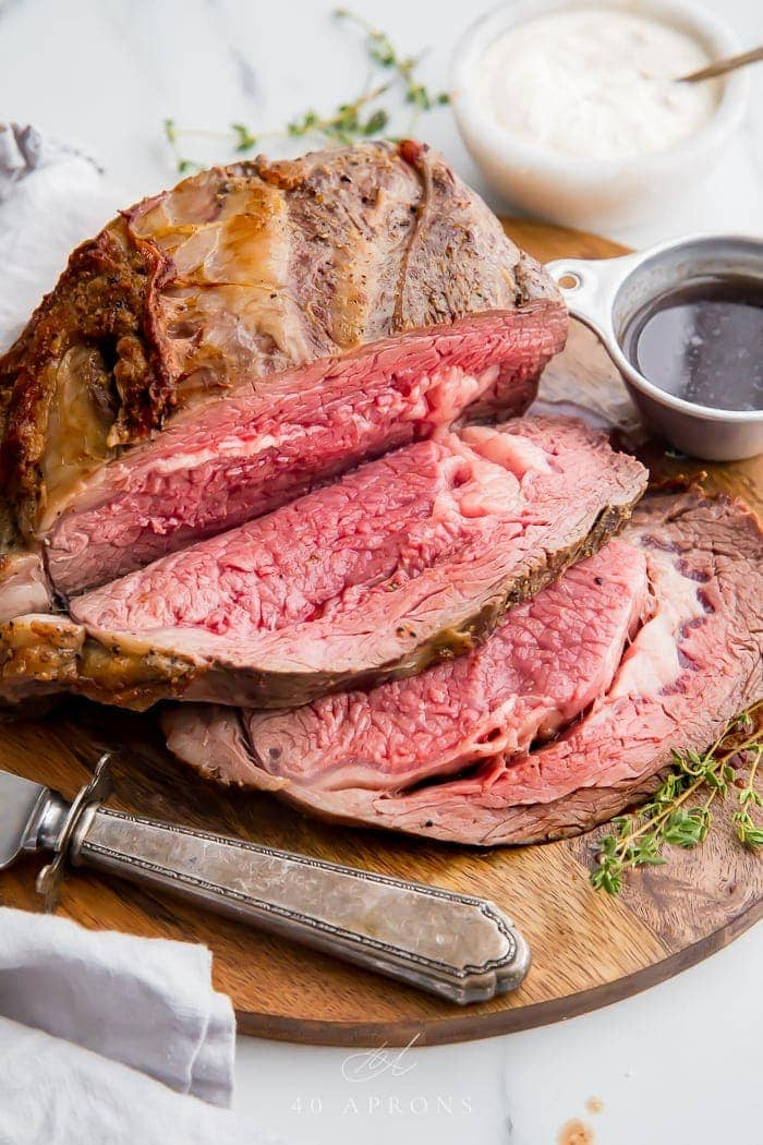 Medium rare prime rib sliced on a board with au jus in a cup