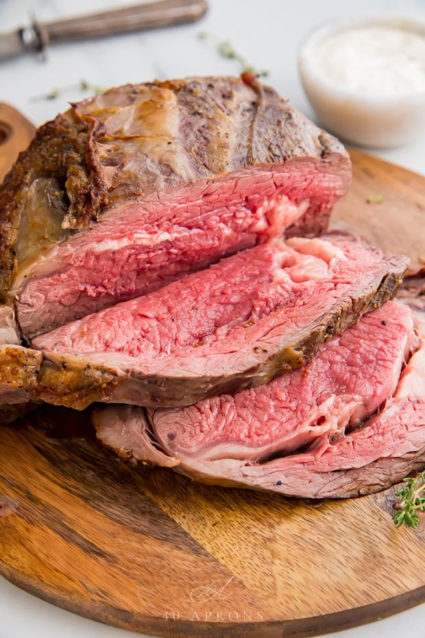 Roasted prime rib in slices on a wooden board