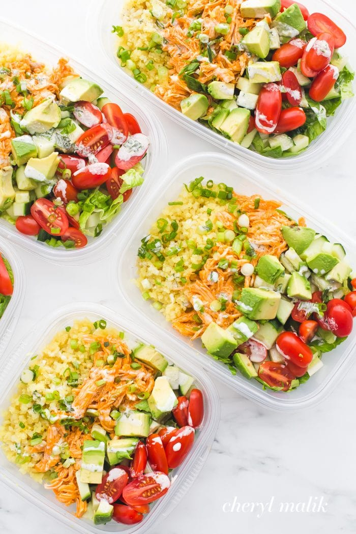 Buffalo chicken Whole30 meal prep recipe with avocado, cauliflower rice, and ranch dressing in container