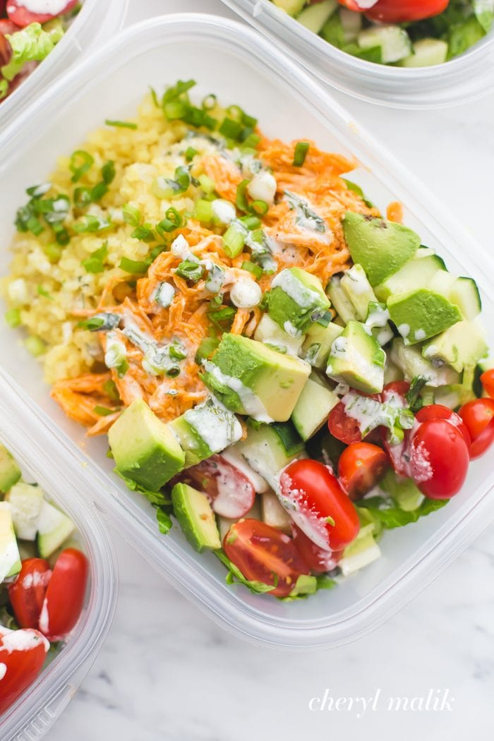 Buffalo chicken meal prep with avocado, cauliflower rice, and ranch dressing in container