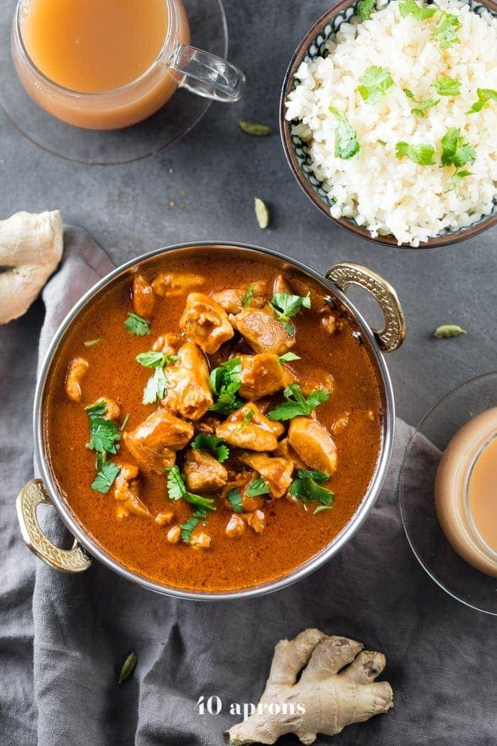 Indian butter chicken in a bowl with cauliflower rice and chai tea
