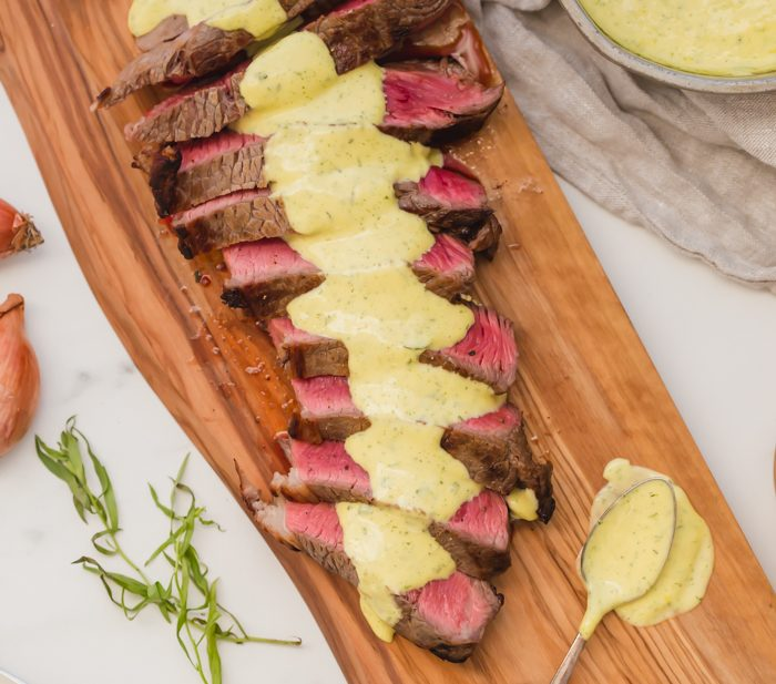 Medium-rare Whole30 steak with Whole30 béarnaise sauce in a dish
