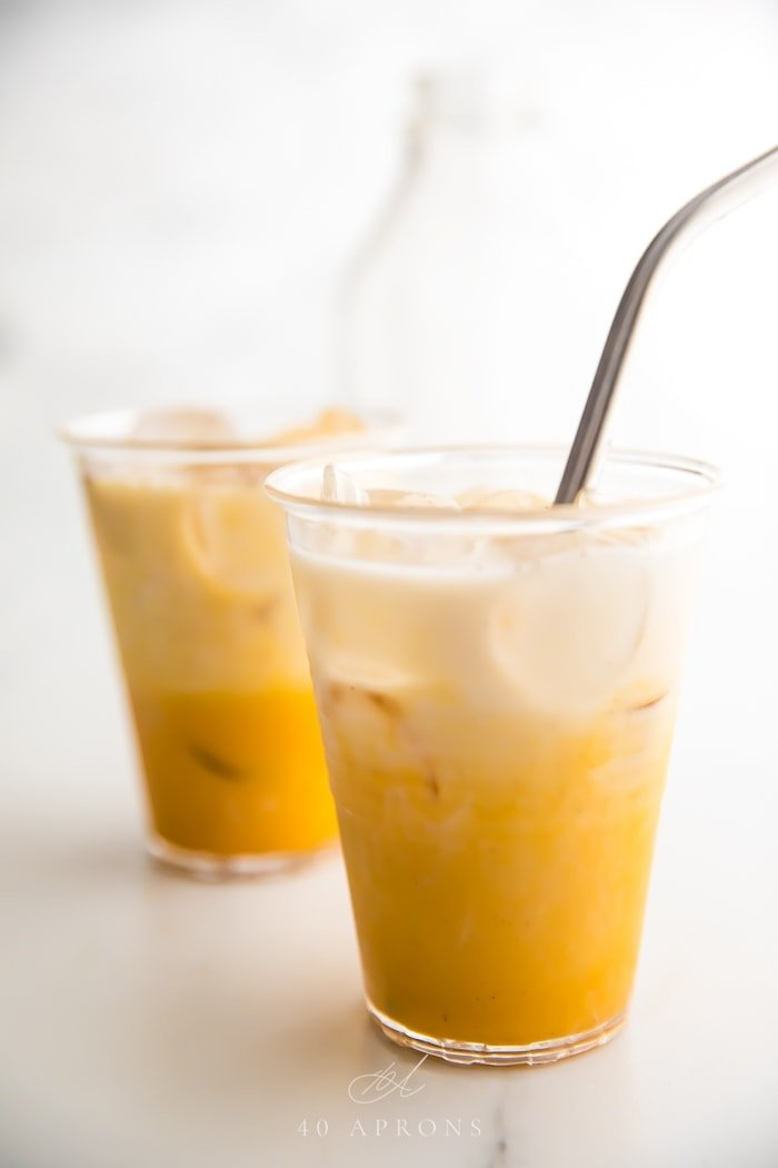 Two iced golden milks in clear plastic cups with straws
