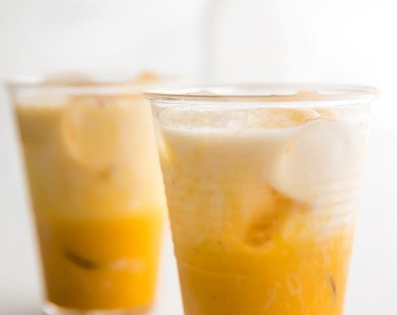 Two iced golden milks on a marble surface