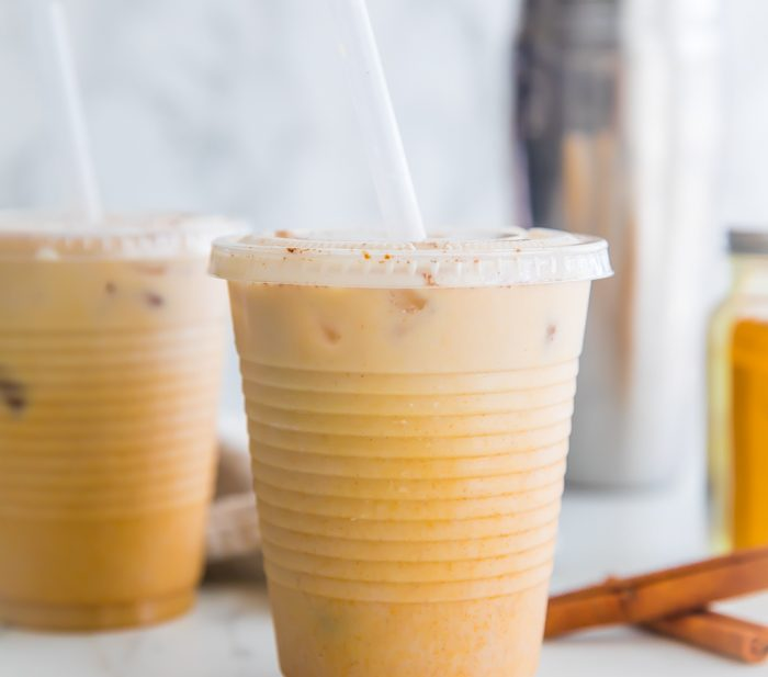 Iced golden milk turmeric latte in plastic cups with straws