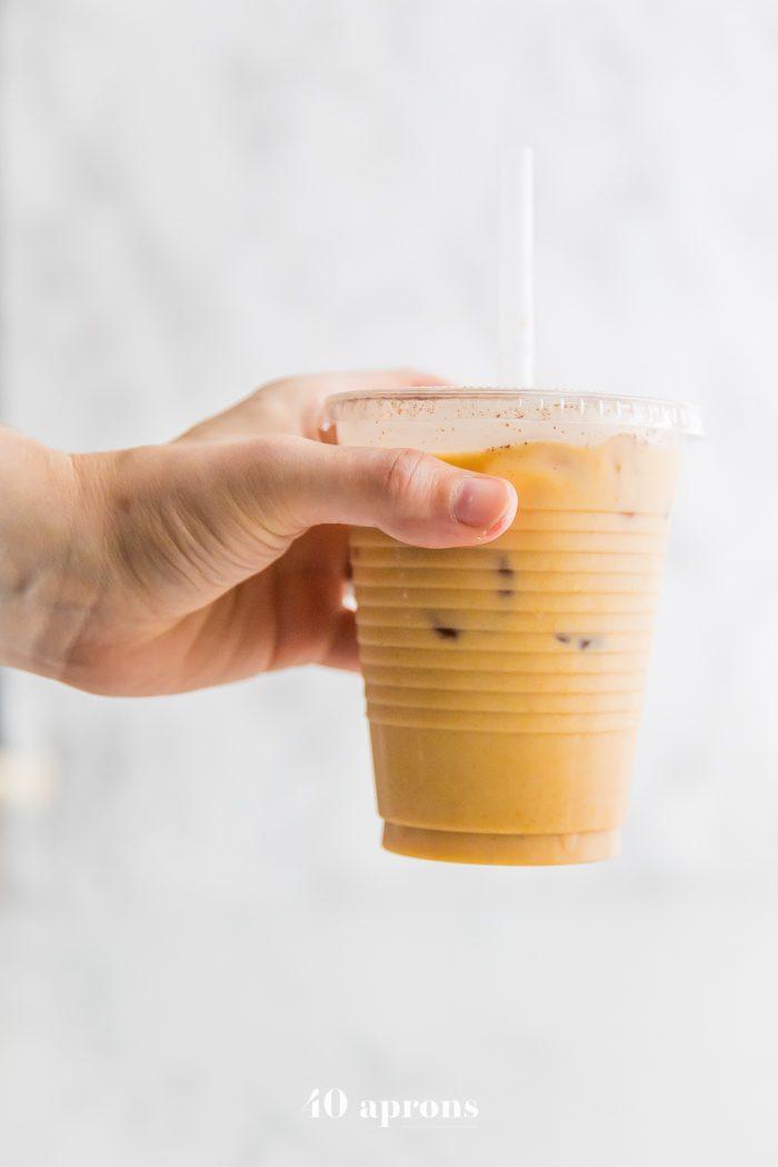 A hand holding an iced golden milk turmeric latte