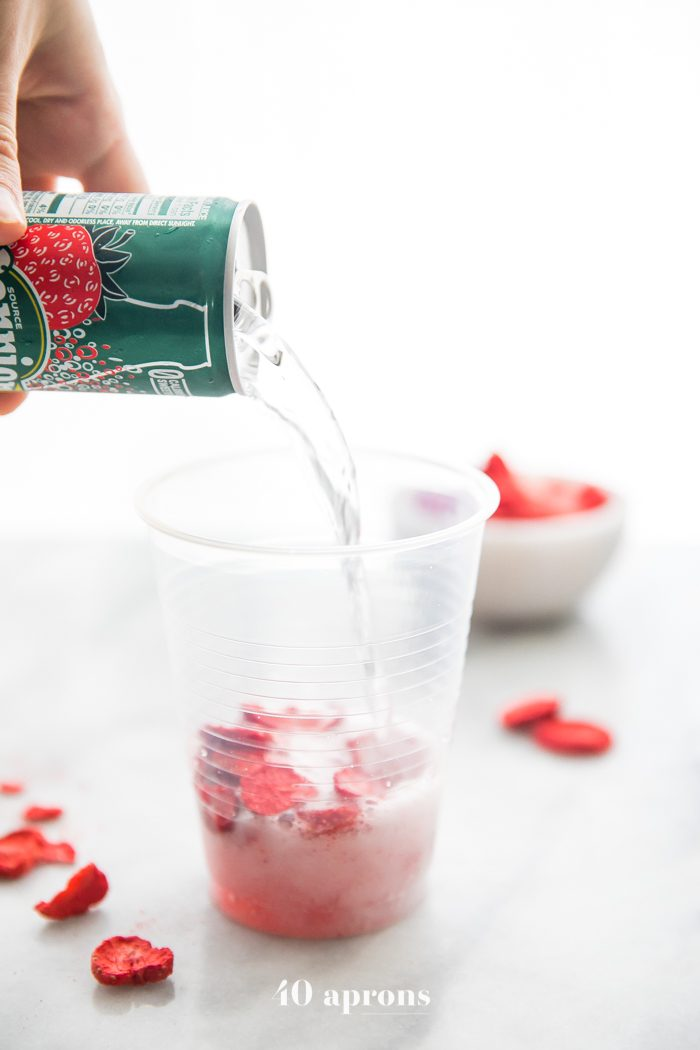 Perrier strawberry sparkling water pouring over freeze-dried strawberries for healthy pink drink