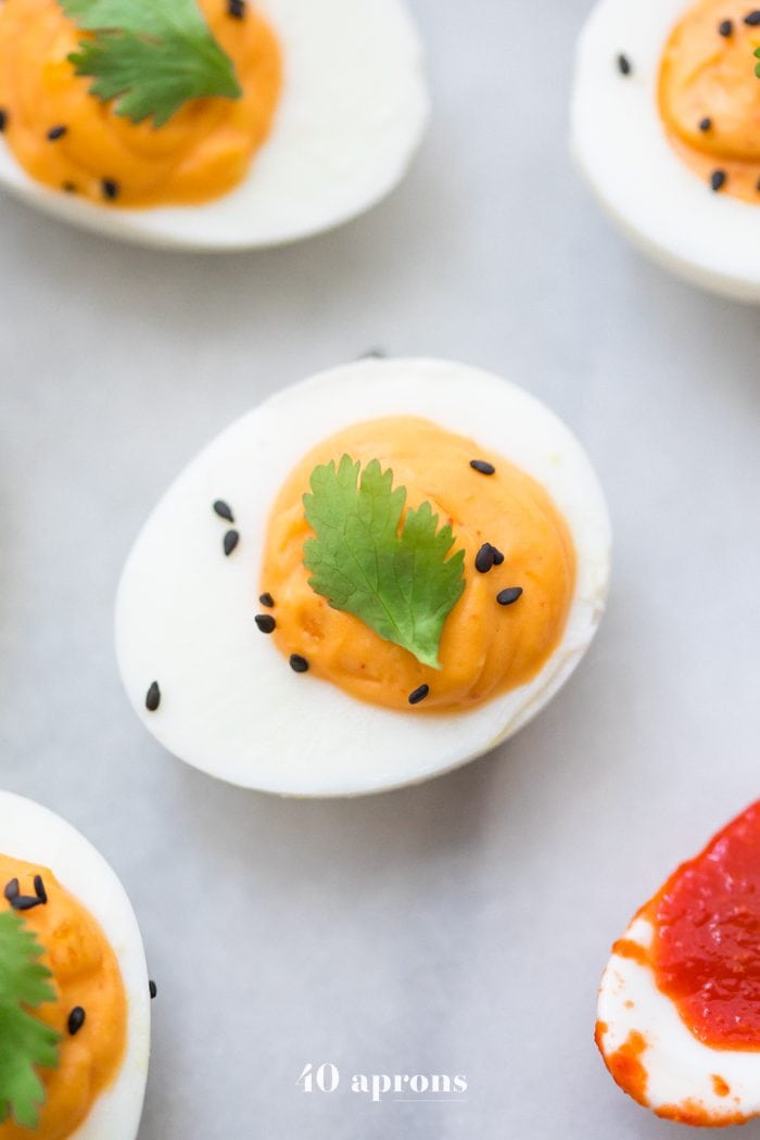 Whole30 sriracha deviled eggs with a spoon of Whole30 sriracha