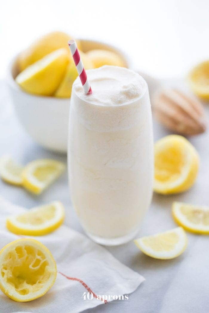 Healthy Chick Fil A frosted lemonade in a glass with a straw and lemons in the background