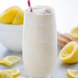 Healthy frosted lemonade in a glass with a straw and lemons in the background