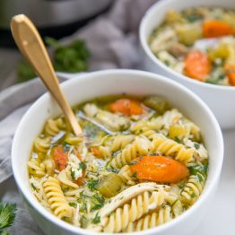 Instant Pot gluten free chicken noodle soup in bowls with Instant Pot in background