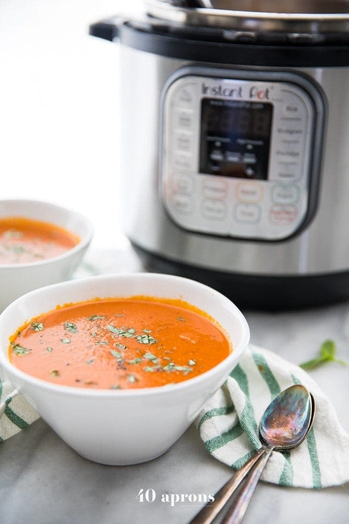 Perfect Whole30 Instant Pot tomato soup (vegan) in two bowls in front of the Instant Pot
