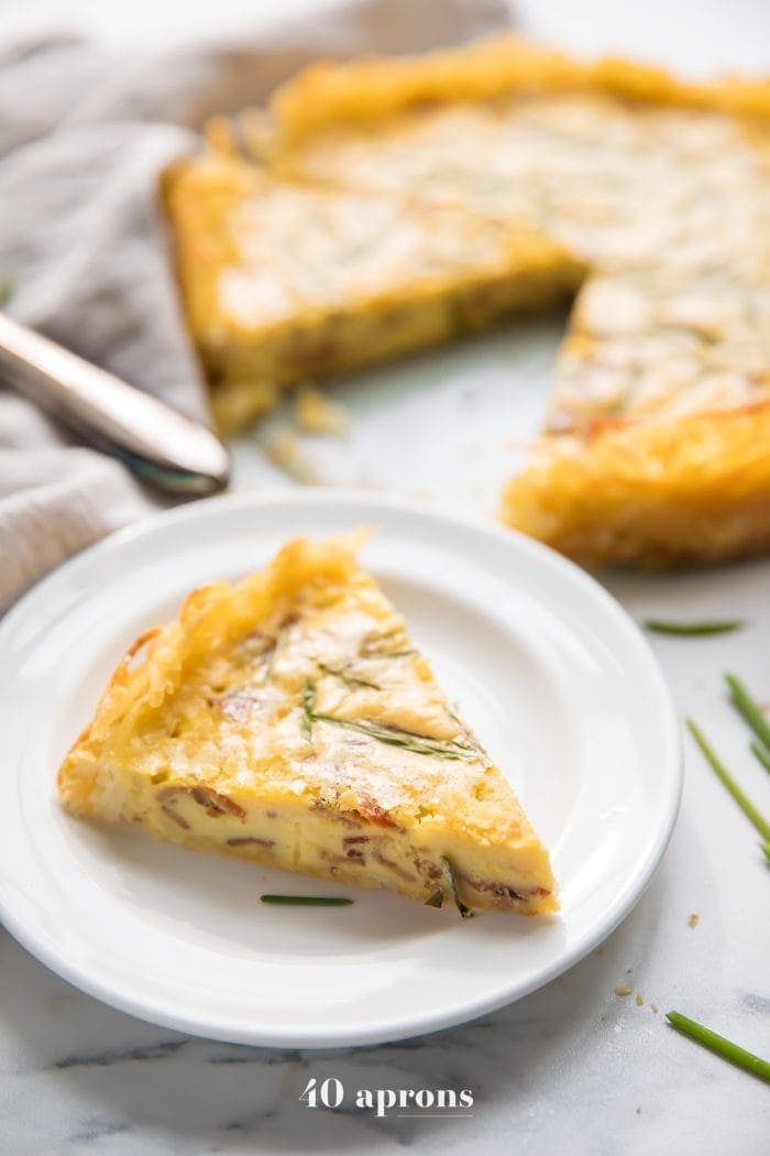 Whole30 quiche lorraine with hash brown crust slice with whole quiche in background