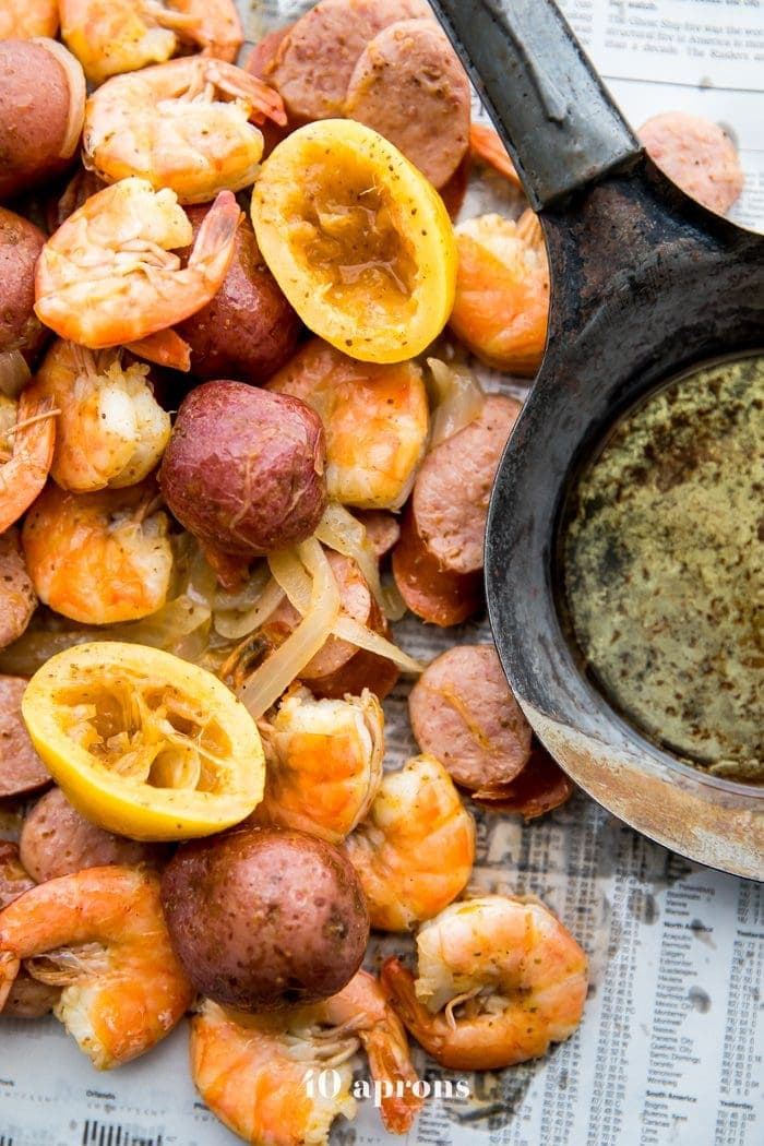 Whole30 shrimp boil with sausage, potatoes, and garlic ghee on newspaper