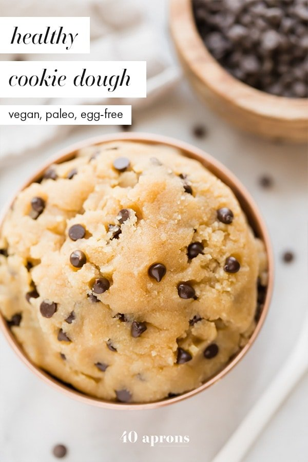 Healthy cookie dough in a copper bowl with a bite taken out and a bowl of chocolate chips in the corner
