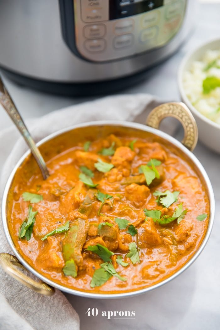 Instant Pot chicken tikka masala in a copper serving bowl in front of Instant Pot with chopped cilantro and cauliflower rice in the background