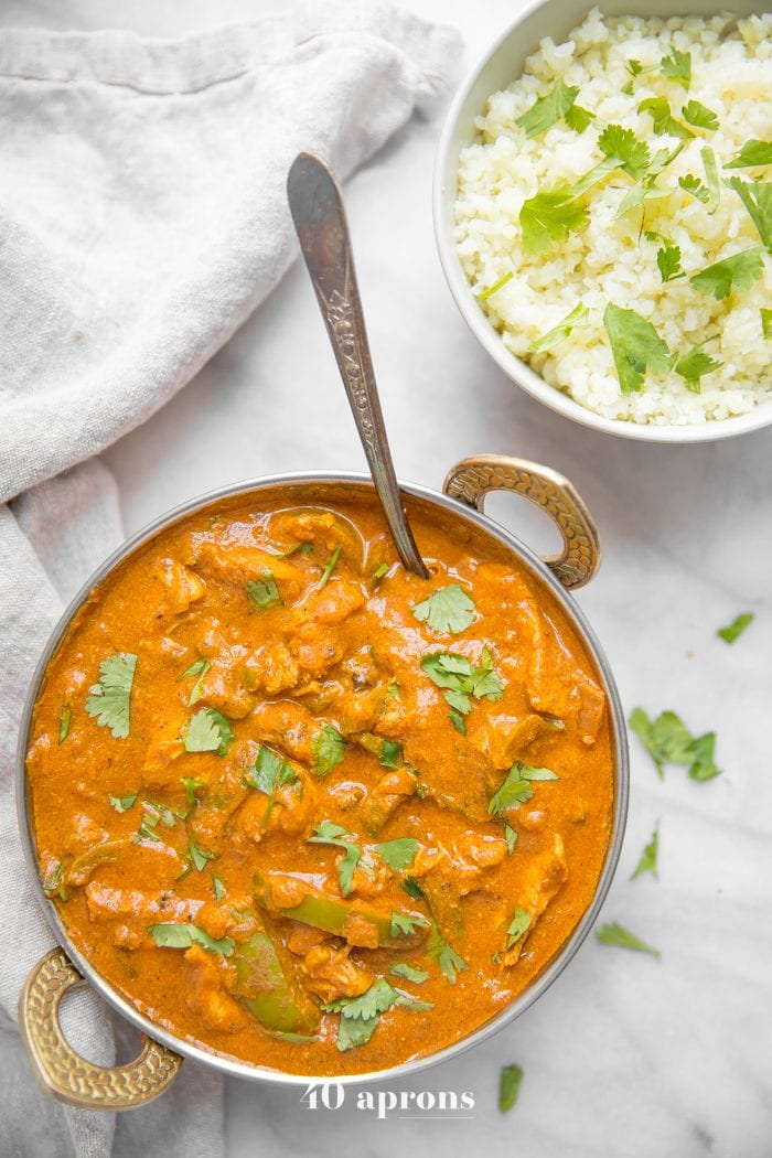 Instant Pot chicken tikka masala in a copper serving bowl with chopped cilantro and cauliflower rice