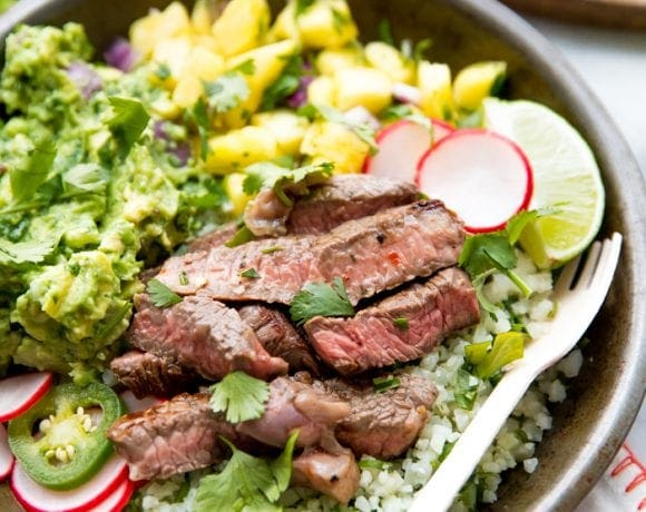 Whole30 steak taco bowl with steak, guacamole, pineapple salsa, pickled radish, and cauliflower rice