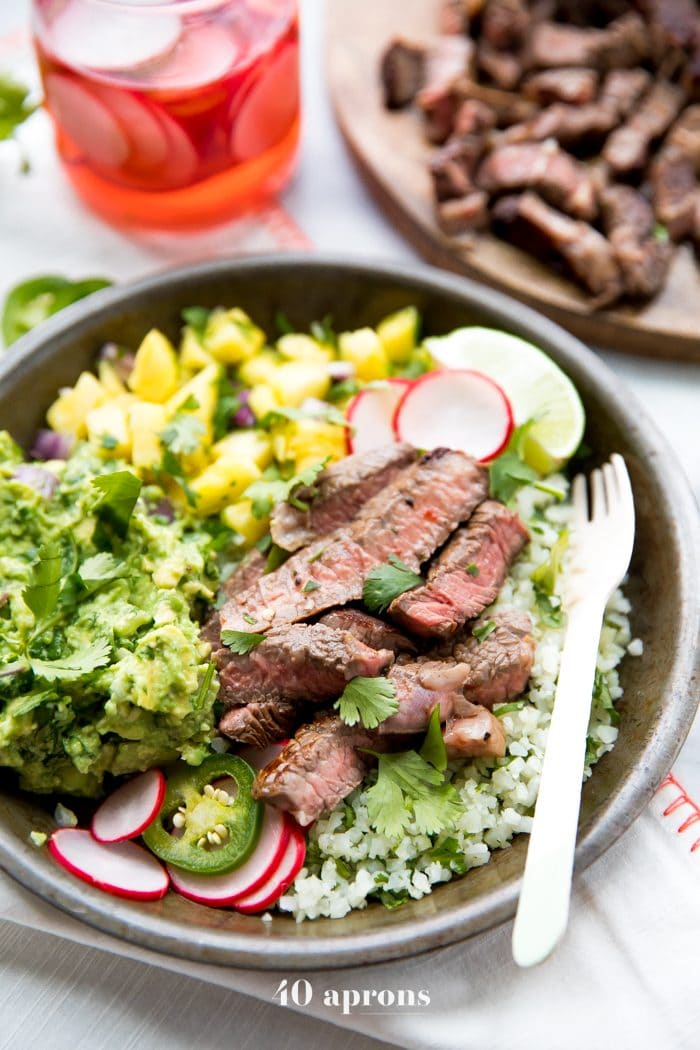 Whole30 steak taco bowls with steak, guacamole, pineapple salsa, pickled radish, and cauliflower rice
