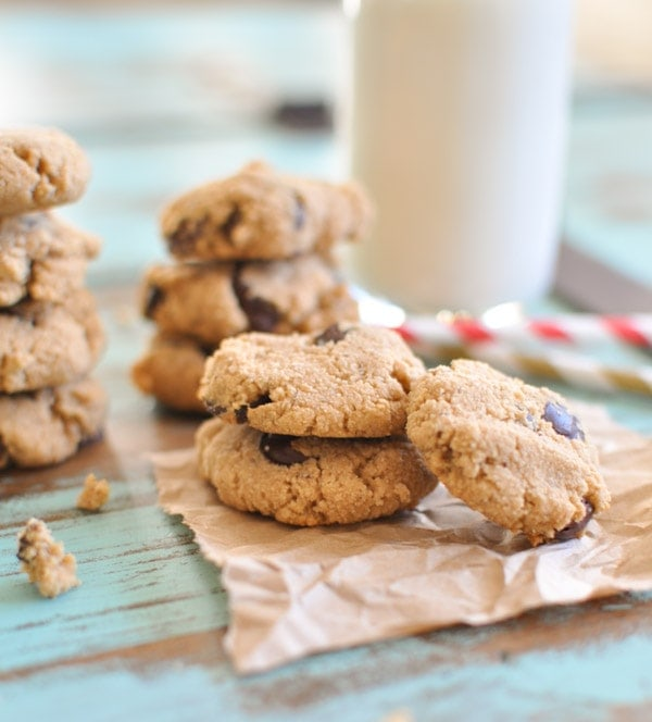 Small Paleo Chocolate Chip Cookies stacked on top of each other placed on brown parchment paper with a glass of milk in the background.