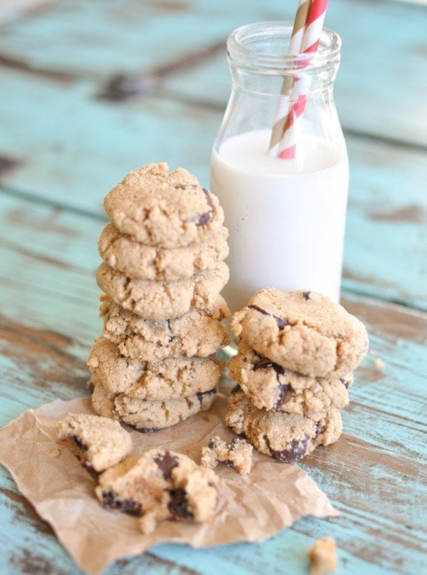 Paleo Chocolate Chip Cookies stacked on top of each other on brown parchment paper leaning against a glass of milk with two straws sticking out.