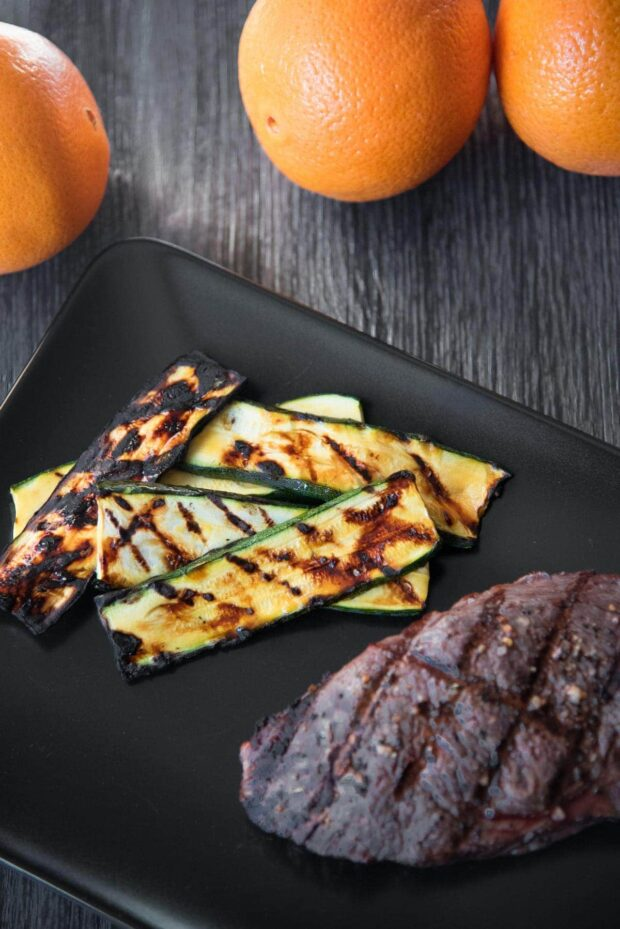 Overhead shot of grill-marked orange glazed grilled zucchini slices arranged on a black plate next to a steak with some oranges in the background.
