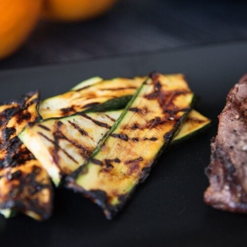 Close-up of slices of orange glazed grilled zucchini crisscross grill marks arranged on a black plate next to a steak.