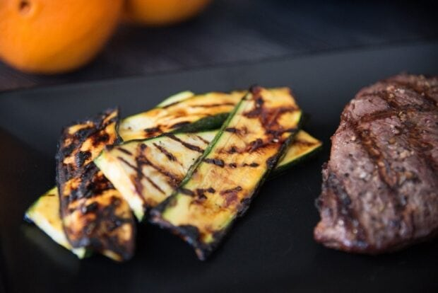 Close-up of grill-marked orange glazed zucchini slices arranged on a black plate next to a steak with oranges in the background.
