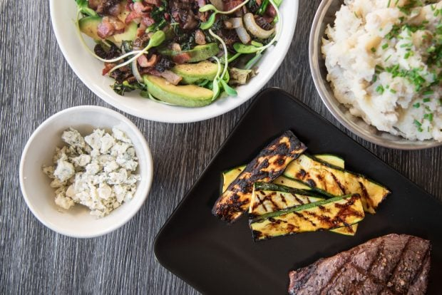 Overhead shot of grill-marked orange glazed grilled zucchini slices arranged on a black plate next to a steak with more BBQ side dishes in the background.