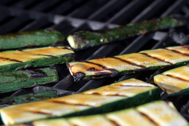 orange glazed zucchini slices cooking on a bbq grill