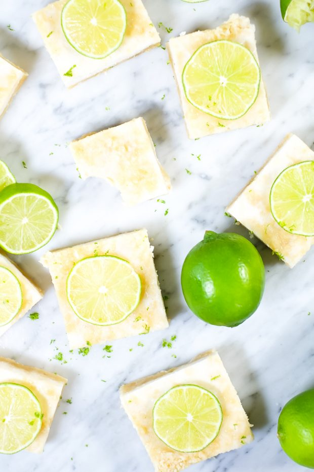 Overhead shot of Paleo Lime Bars decorated with thin lime slices and placed on a marble counter top
