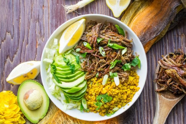 Instant Pot Brisket Taco Bowl topped with avocado slices and chopped green onions placed on a rustic wooden tabletop.