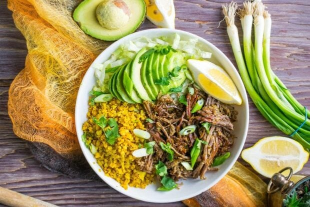 Instant Pot Brisket Taco Bowl topped with avocado slices and chopped green onions placed on a orange shawl on a rustic wooden tabletop.