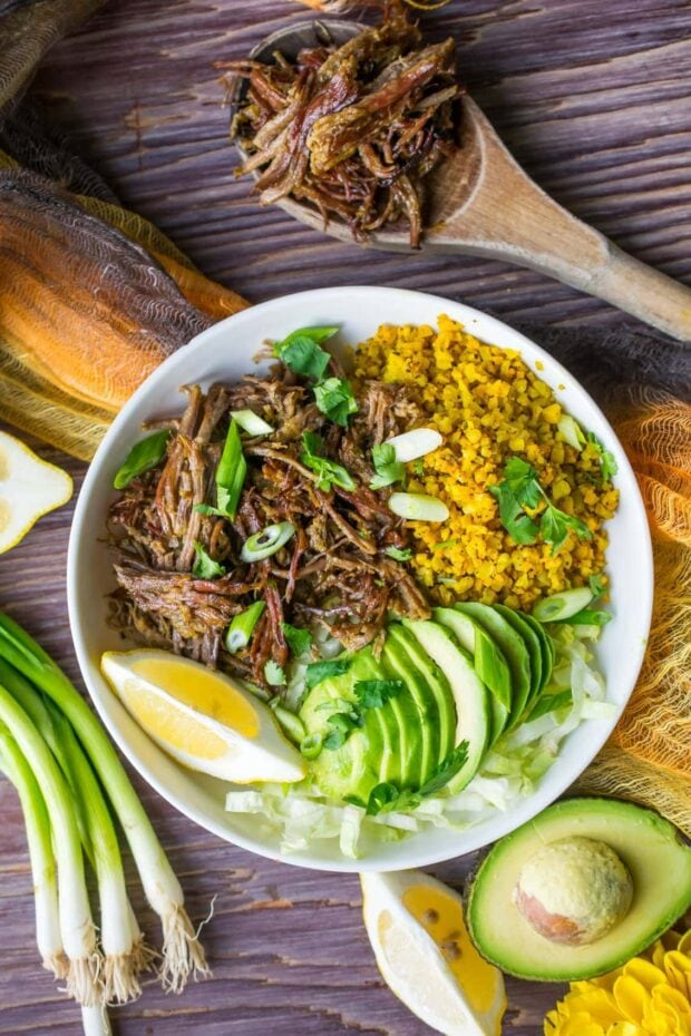 Instant Pot Brisket Taco Bowl topped with avocado slices and chopped green onions placed on a rustic wooden tabletop with some ingredients surrounding it.
