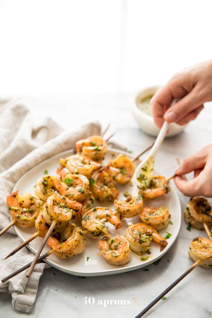Hands drizzling chimichurri sauce on chimichurri shrimp skewers, piled on a plate