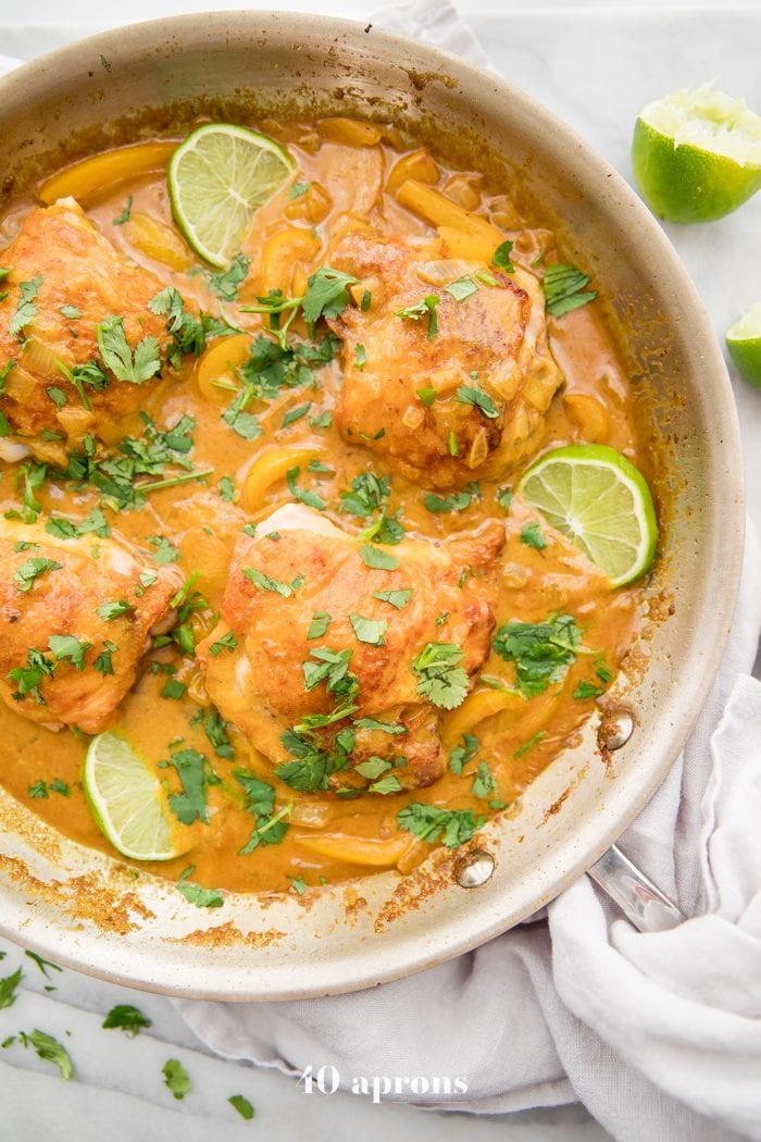 Coconut curry turmeric chicken in a pan with cilantro garnish and a lime to the side