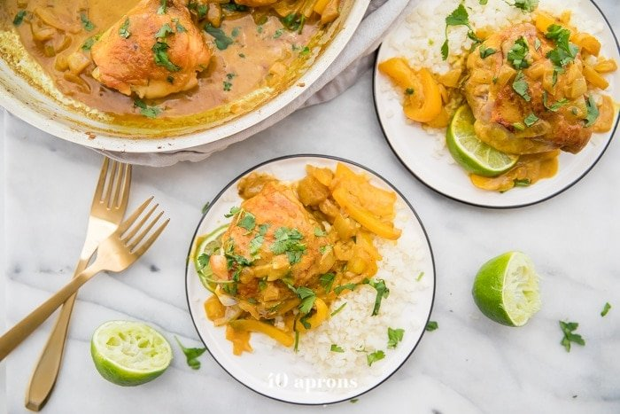 Coconut curry turmeric chicken on a plate with cilantro garnish and a lime to the side