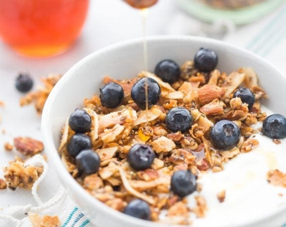 Bowl of the crunchy paleo granola recipe over yogurt, topped with blueberries and a drizzle of honey
