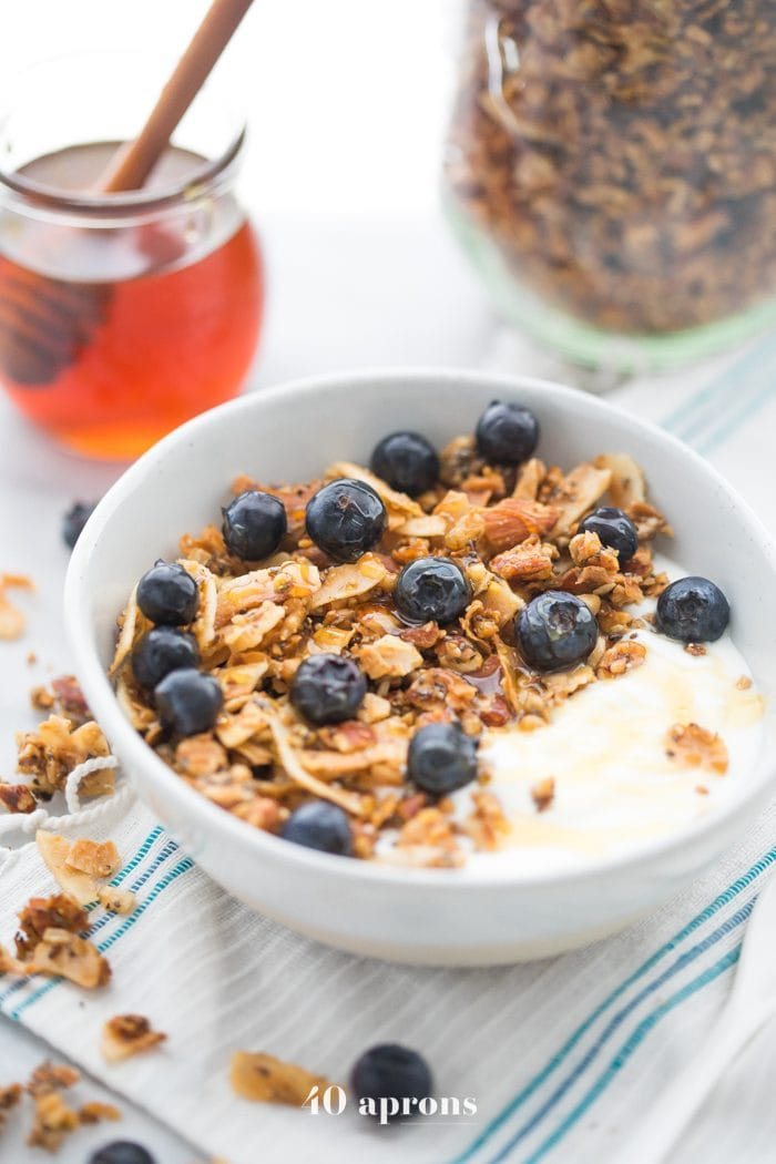 Bowl of the crunchy paleo granola recipe over yogurt, topped with blueberries