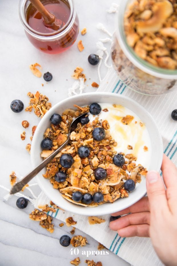 Hand holding a bowl of the crunchy paleo granola recipe over yogurt, topped with blueberries and a drizzle of honey