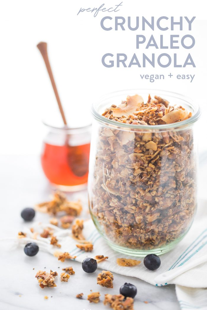 A glass jar of a crunchy paleo granola recipe with a jar of honey in the background