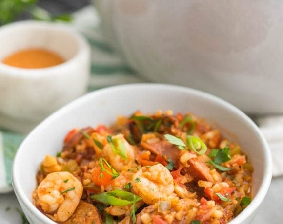 Whole30 healthy jambalaya with cauliflower rice in two bowls and a Dutch oven