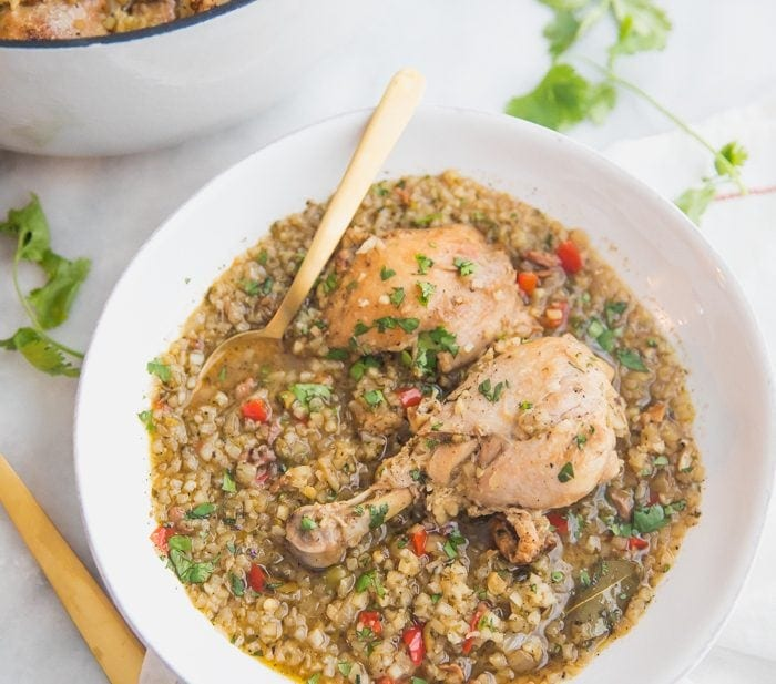 Healthy Spanish chicken and rice stew in a bowl with a pot of the stew next to it