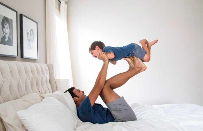 Dad in bed holding toddler on his feet up in the air