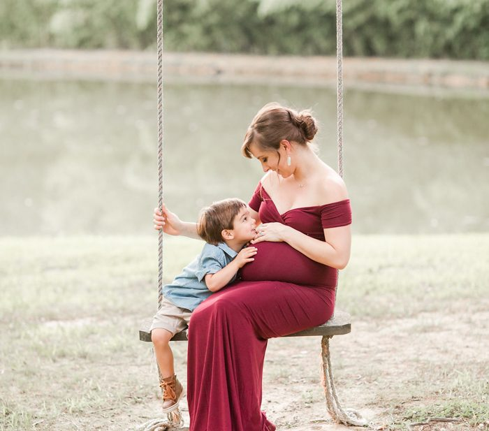 Toddler and pregnant mom on a swing in front of a lake