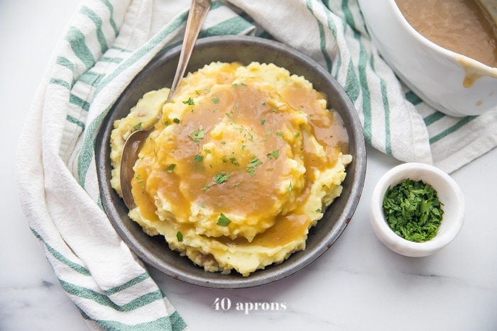 creamy mashed potatoes smothered with a rich paleo gravy served in a grey dish with a dishtowel wrapped around it and a small dish with chopped chives on the side.