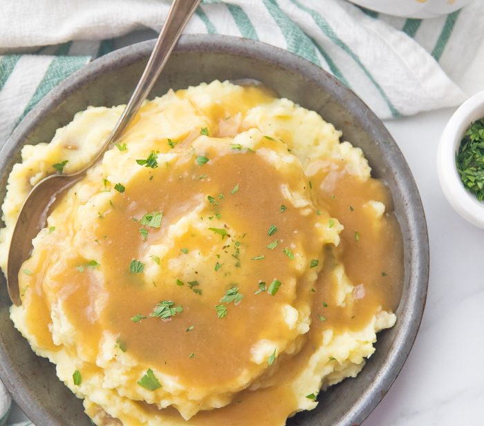 bowl of creamy mashed potatoes topped with a rich Paleo Gravy and some chopped chives