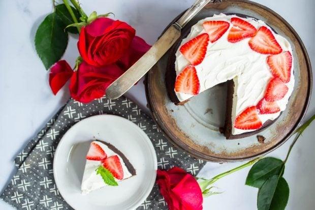 overhead shot of a flourless paleo keto chocolate dessert torte on a cake stand with one slice cut