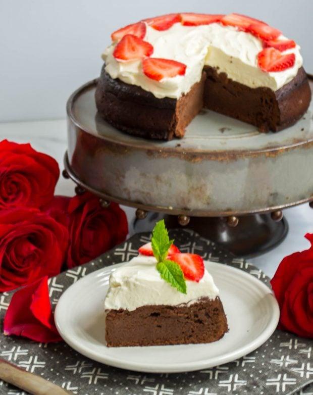 keto flourless chocolate cake on a cake stand with one slice cut