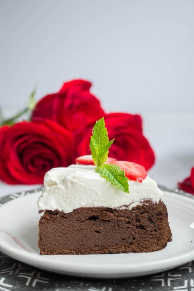 side view of a slice of keto flourless chocolate cake with whipped cream on a white plate